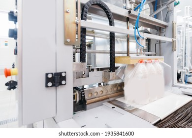 Dairy factory industry, automatic packaging of bottles with milk in plastic bags.