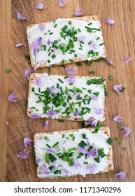 Dairy and lactose-free vegan cream cheese spread made from cashew and macadamia nuts on crackers with fresh chopped chives and edible chive flowers on a wooden chopping board