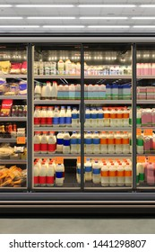 Dairy product in Glass door fridge Horizontal photo mockup yogurt and milk and plastic diary bottles in vertical freezer at supermarket. Suitable for presenting new Dairy packaging or label design