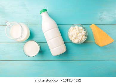 Dairy products. Cottage cheese, cheese, milk and kefir on blue wooden background with copy space.