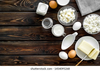 Dairy products from farm with milk, eggs, cottage, butter, yougurt on wooden background top view mockup