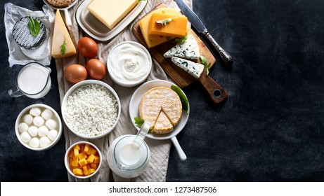 Dairy products.  Milk, cheese, sour cream, cottage, yogurt and butter on dark background. Flat lay with copy space