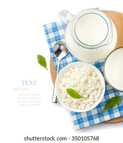 Dairy products, milk in a glass and pitcher, cottage cheese in a bowl,  checkered napkin  on a white background, top view , closeup