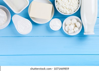 dairy products on blue wooden background, top view