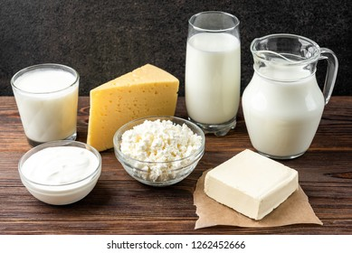 Dairy products on dark wooden background. Milk, kefir, cheese, cottage cheese, butter and sour cream.
