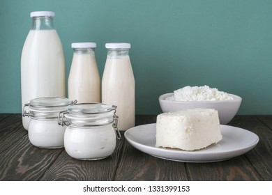 dairy products on a wooden table: milk, butter, cottage cheese, yogurt