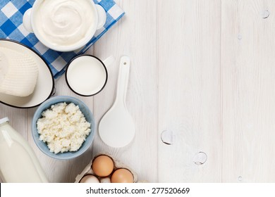 Dairy products on wooden table. Sour cream, milk, cheese, eggs and yogurt. Top view with copy space
