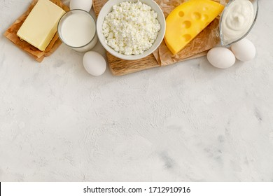 Dairy products and raw eggs on white background. Top view. Copy space.