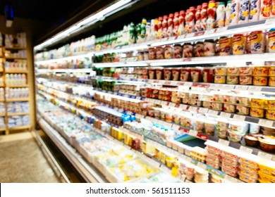 Dairy products in refrigerator of supermarket. Refrigerator with dairy products in supermarket. Blurred background.
