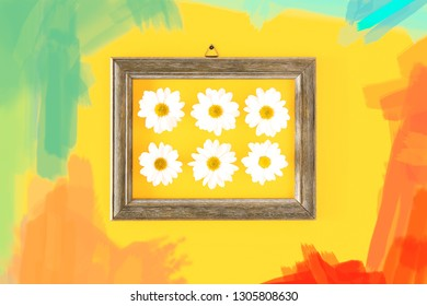 Daisies in wooden frame surraunded by brush strokes of color paint trends on  yellow interior wall background - Colorful spring concept with trendy pastel colour tones - Image