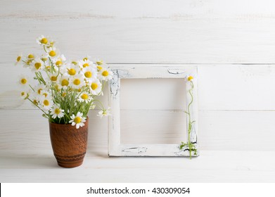 Daisy flowers bouquet and photo frame on white wooden shabby board. Home interior.