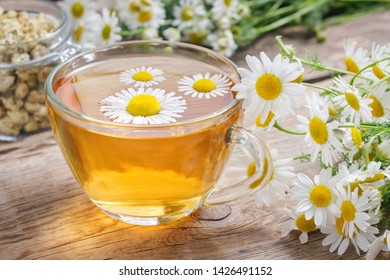 Daisy flowers in transparent glass tea cup, healthy chamomile herbs and glass jar of dry daisies buds.