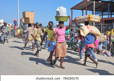 Dajaban / Haiti - July 15, 2011: Haitian woman carries a bucket of goods on her head while men carry a poultry crate and sack of grains at Haitian / Dominican Republic border market.