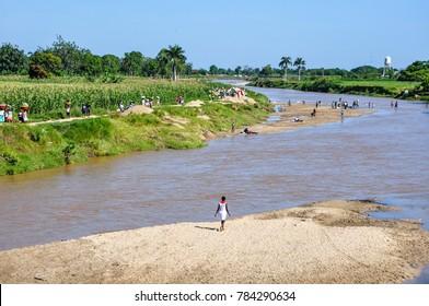 Dajabon /Haiti - July 15, 2011: solitary Haitian woman crossing muddy river bank at Haiti and Dominican Republic border.