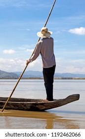 Dak Lak, VIETNAM - JANUARY 6, 2015 - Man pushing a boat with a pole