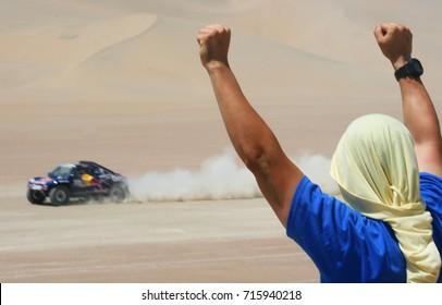 Dakar rally fan watching car goes by