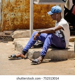 DAKAR, SENEGAL - APR 23, 2017: Unidentified Senegalese man in cap sits on the ground and listens to music in Dakar, the capital of Senegal