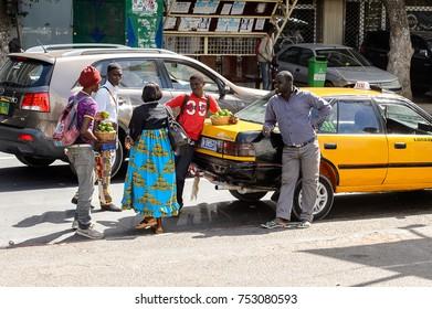 DAKAR, SENEGAL - APR 23, 2017: Unidentified Senegalese people stand near the yellow car in Dakar, the capital of Senegal