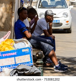 DAKAR, SENEGAL - APR 23, 2017: Unidentified Senegalese men sit beside the road in Dakar, the capital of Senegal