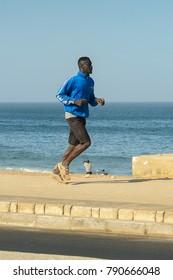 DAKAR, SENEGAL - APR 23, 2017: Unidentified Senegalese man runs along the shore of the ocean in Dakar, the capital and main city of Senegal