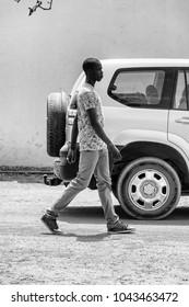 DAKAR, SENEGAL - APR 27, 2017: Unidentified Senegalese tall man walks along the road near the car in the Village des Arts in Dakar