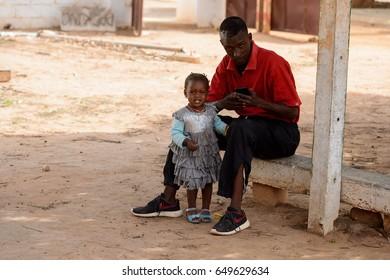 DAKAR, SENEGAL - APR 27, 2017: Unidentified Senegalese little girl cries near her father in the Village des Arts in Dakar