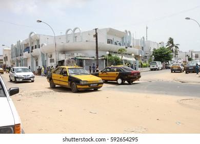 Dakar, Senegal - August 31, 2012: People and cars in a sandy street in the commune d'arrondissement Patte d'Oie of the city of  Dakar in Senegal