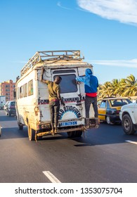 Dakar, Senegal - February 2, 2019: Everyday life in Senegal. Old microbus circling the roads, with the passengers on the back door. Dakar, Senegal. Africa.
