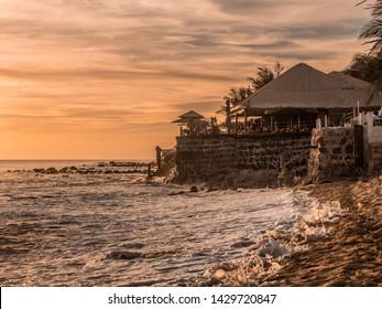 Dakar, Senegal - February 2, 2019: Sunset on the Atlantic coast in Dakar and the silhouette of a coastal restaurant in the background, Senegal, Afrika