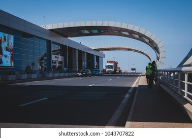 DAKAR, SENEGAL, FEBRUARY 22 2018: Departure platform on the new Blaise Diagne airport in Dakar, Senegal on a sunny day. Some people, security guards and cars are seen parked.