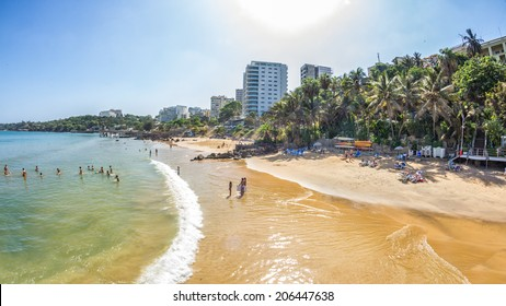 Dakar, Senegal - July 2014: Tourists and the local residents of Dakar spend their holidays on the beautiful beaches on July 11, 2014 in Dakar, Senegal