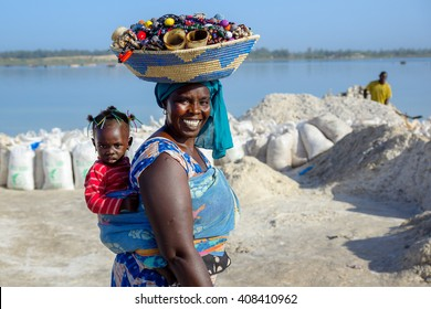 DAKAR/SENEGAL - NOVEMBER 12, 2013: Senegalese smiling woman with a basket of handmade jewelry and souvenirs for sale on her head and a baby on her back at the Retba salt lake near Dakar, Senegal
