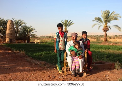 Dakhla Oasis, Egypt - April 2nd of 2015: A bedouin family posing in front of the camera with their own land backwards. During centuries bedouin society has ruled in the western egyptian desert.