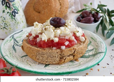 Dakos traditional Greek appetizer on a traditional plate with ceramic olive oil jar, dry rye bread, olives and olive branch. Healthy eating concept. Mediterranean lifestyle.