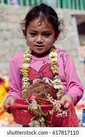 DAKSHINKALI, NEPAL - MAY 11, 2013: Nepalese girl carries offering to the temple in Dakshinkali village, Kathmandu valley, Nepal.