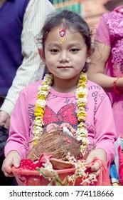 DAKSHINKALI, NEPAL - MAY 11, 2013: Nepalese girl carries offering to the temple in Dakshinkali village, Kathmandu valley