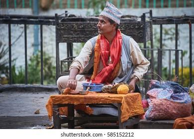 DAKSHINKALI/NEPAL - NOVEMBER 14, 2016:  Nepalese craftsman with topi hat and red scarf sitting in Dakshinkali hindu temple in Pharping, Nepal