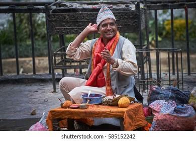 DAKSHINKALI/NEPAL - NOVEMBER 14, 2016: Smiling nepalese man with topi hat and red scarf sitting in Dakshinkali hindu temple in Pharping, Nepal