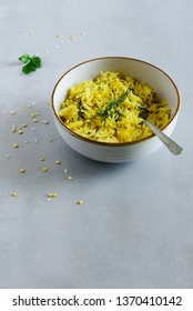 Dal khichadi or Khichdi Tasty Indian recipe served in bowl over grey background is made of yellow lentil dal (moong dal) and rice combined  and cooked as one pot meal.  Image