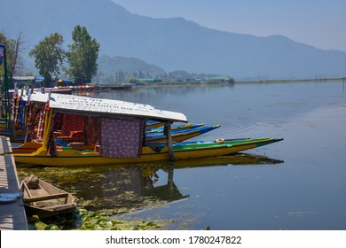 Dal Lake, Srinagar, Jammu and Kashmir, India - 06/27/2019 : Beautiful shikara parked in dal lake. Amazing landscape view of dal lake with reflection of shikara , trees, sky in water. Heaven of India.