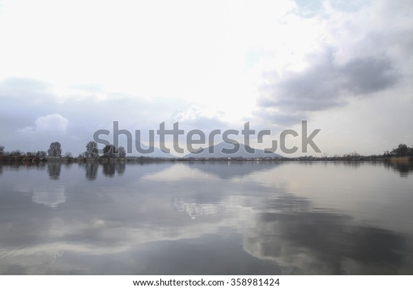 Dal Lake, Srinagar, Kashmir is renowned for its mirror like qualities reflecting mountains, clouds, Chinar trees and houseboats, CIRCA 2012