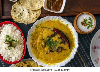 Dal tadka served with steam rice, papad, lal mirch ka achaar, a glass of chaas