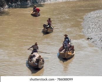 Dala, Myanmar - November 5, 2017: Small, traditional fishing vessels with husband and wife teams padling down Dala River near Yangon.