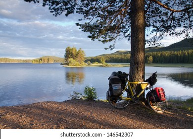 DALARNA, SWEDEN - JUNE 18: Biker established tent by the lake in Dalarna state, Sweden on June 18, 2012. Unlimited access to nature allows to put up a tent almost everywhere.