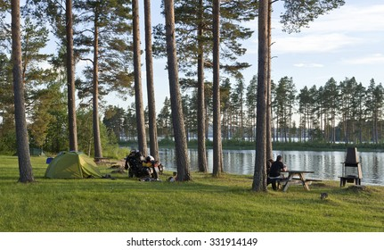 DALARNA, SWEDEN ON JULY 02. Camping in tent close to a lake on July 02, 2015 in Dalarna, Sweden. Unidentified couple on MC relax in the evening