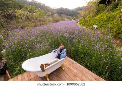 Dalat city, Vietnam - January 14th 2020:  Visitors sit on a bath in the middle of a field of purple flowers