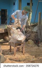 DALAT, VIETNAM - DECEMBER 29, 2015: Carver handles wooden sculpture in the Studio
