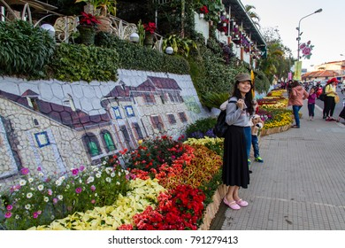Dalat, Vietnam - December 30, 2015 : Tourists enjoy to selfie and take photo with flower. Dalat city is decorated by flower for New Year coming and Flower Festival
