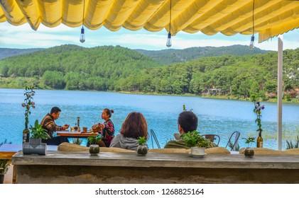 Dalat, Vietnam - Nov 12, 2018. People sitting at lakeside coffee shop in Dalat, Vietnam.