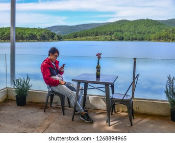 Dalat, Vietnam - Nov 4, 2018. A young man sitting at lakeside coffee shop in Dalat, Vietnam.